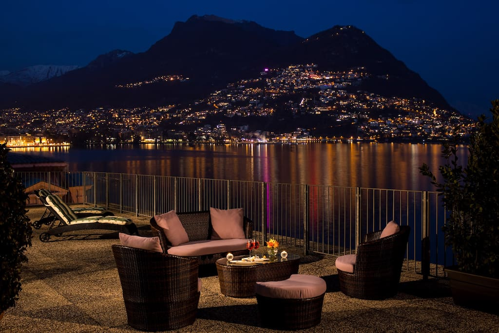 The large terrace at night offers unparalleled views over Lake Lugano and the City