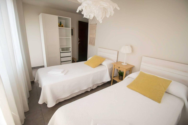 Dormitorio 2 con dos cómodas camas individuales. Tiene salida directa al balcón y da a dos de las tres calles que da el apartamento. Muy luminoso y alegre!