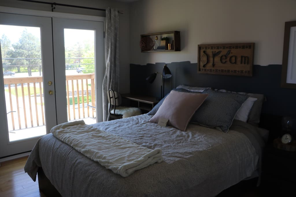 Room #1 Scandinavian Room - Queen bed with available desk space. South facing window with dark curtain for privacy and ability to sleep in undisturbed. Shelving space and Hanging available, more so than Room 2 so choose this room if you need more storage of clothing