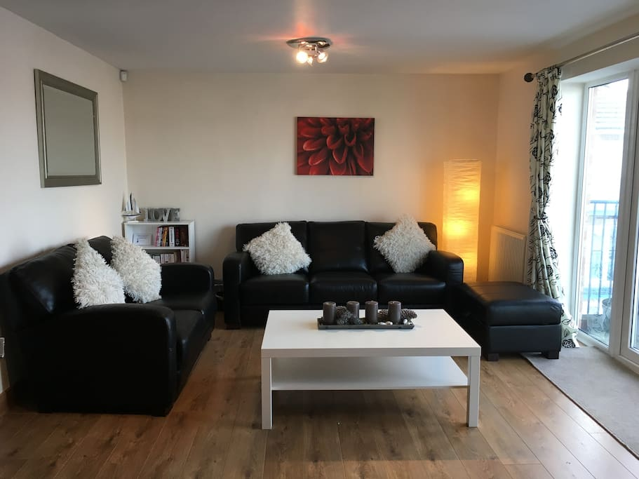 "Sitting room: digital Smart 42"" TV, Blu-ray DVD player, 3 and 2 seater sofas, French doors leading to balcony"