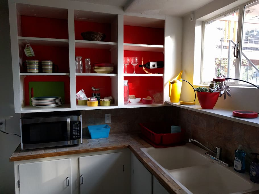 Kitchen with microwave, dishes and plenty of snacks