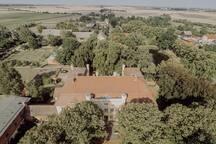 Unser Schloss, umgeben von Bäumen und Wiesen. Der Park erstreckt sich in die andere Richtung.