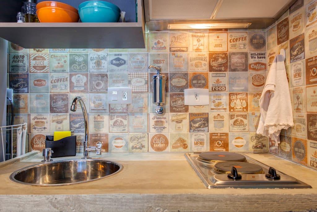 Bancada da pia: Cooktop, depurador, cuba de inox, torneira, dispenser de sabão e filtro de água.