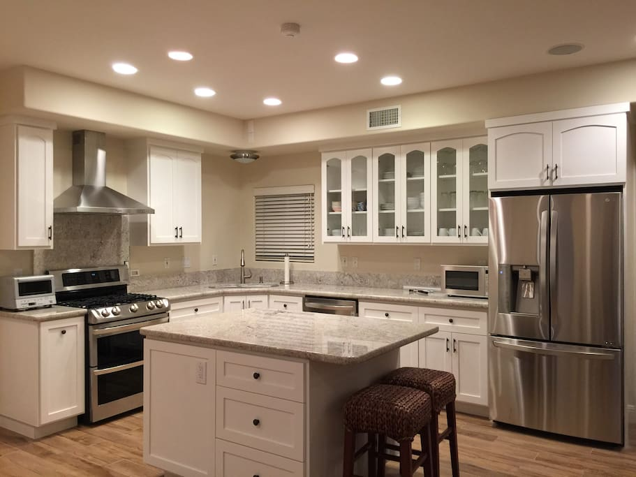 Brand new kitchen with stainless steel appliances, utensils and dinnerwares