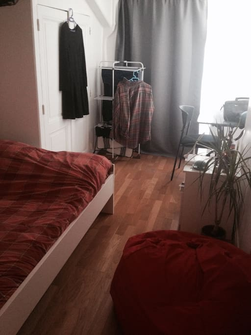 Chambre lumineuse avec grand lit et bureau.