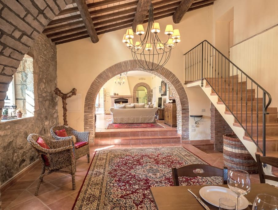 The capacious ground floor has an open floor plan with brick arches separating the living room from a large dining hall with a country style kitchen.