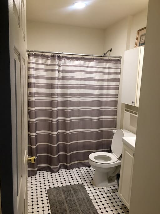 Clean bathroom with tub/shower and full length mirror.