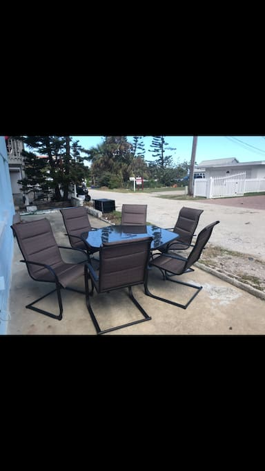 Back patio  has a large outdoor table with relaxing rocking chairs.