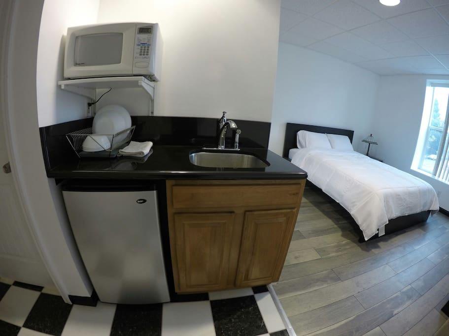 Private mini kitchenette area. Mini fridge, microwave, toaster, plates, cups, utensils, and sink