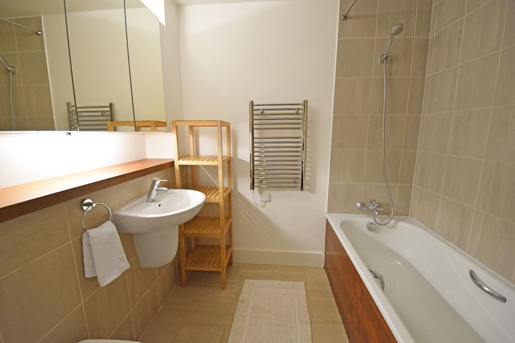 Bathroom with bath tub and towel warmer