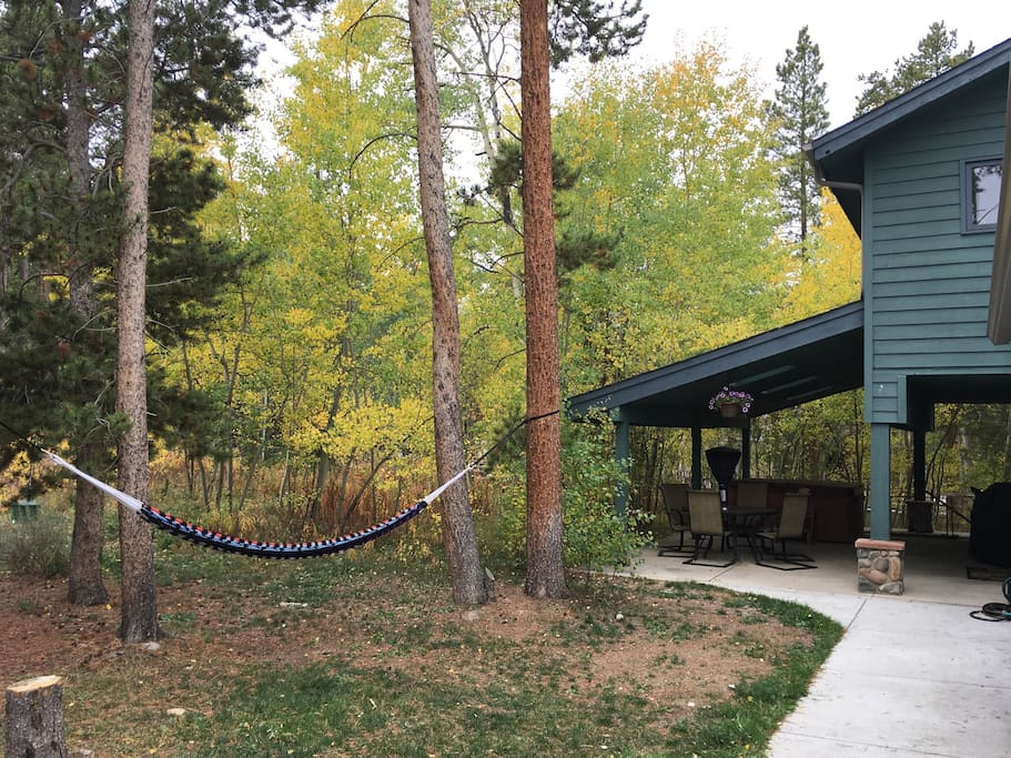 Access to the backyard with hammock, patio table, and hot tub