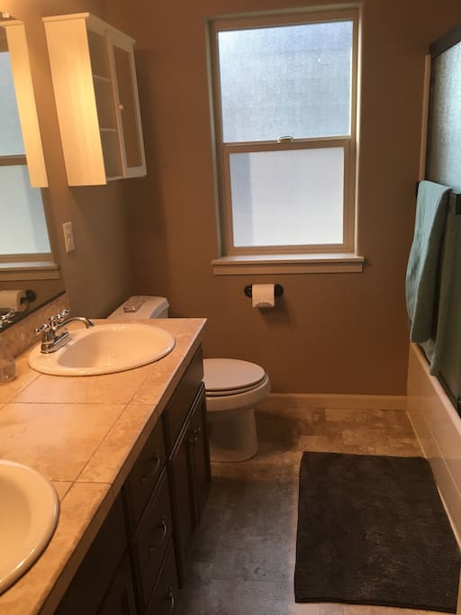 Clean bathroom with dual sinks and detachable shower head