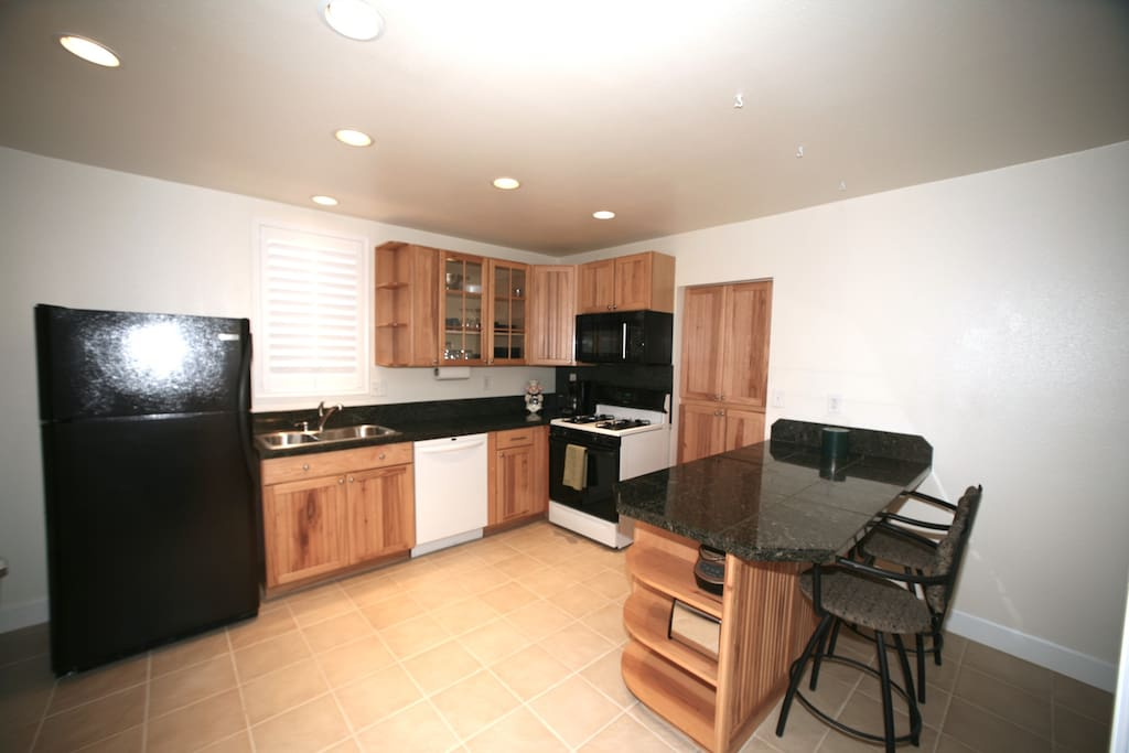 Beautiful hickory and granite kitchen stocked with lots of utensils, pots & pans, slow cooker, coffee machine, etc.
