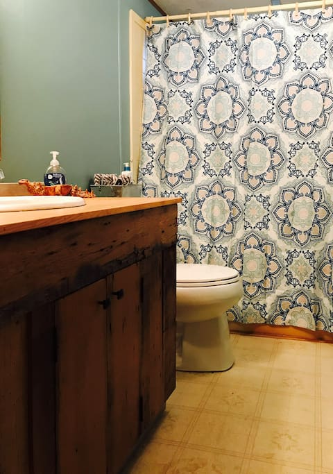 Bathroom with custom cabinet built from barn boards found on the land.