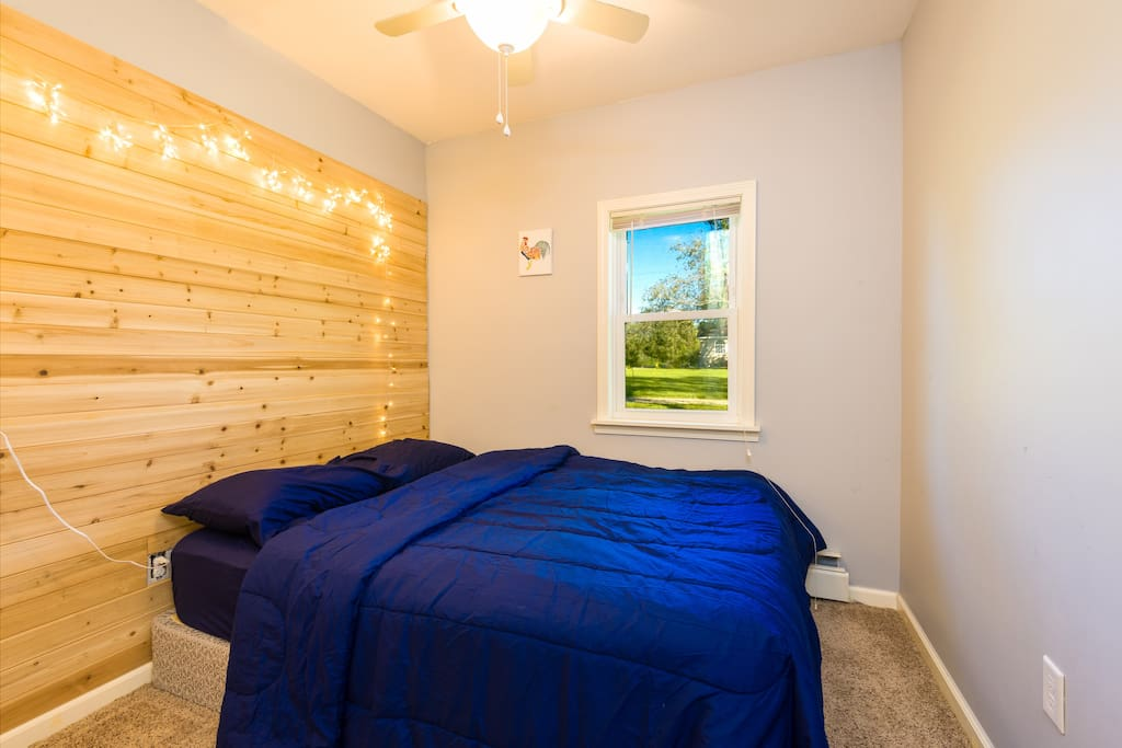 Room is 10 ft x 10 ft (+ entry way) with wood accent wall, window, ceiling fan, and closet