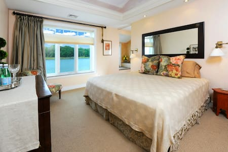 Egret Bedroom with king bed, large window with magnificent water view, private bath with air jet tub, tray ceiling