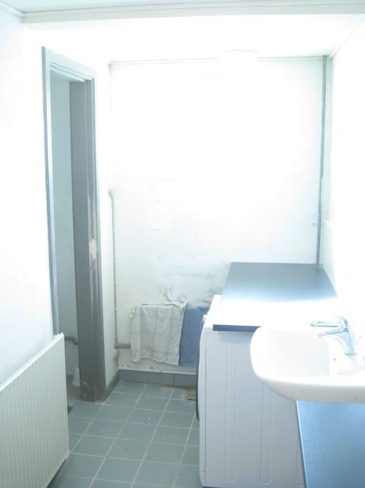 Bad, bruserum, bordplade og vaskemaskine. 3 personer deler badet
