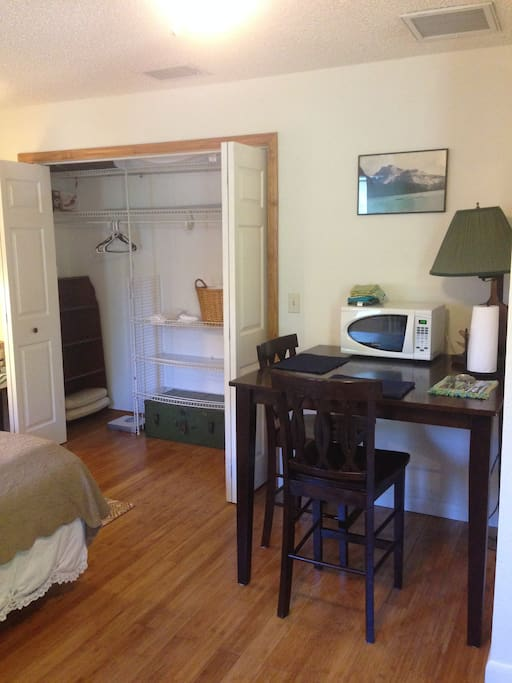 Large closet with hangers, spare pillows, blankets, towels, and washcloths. Dining nook on the right with microwave.