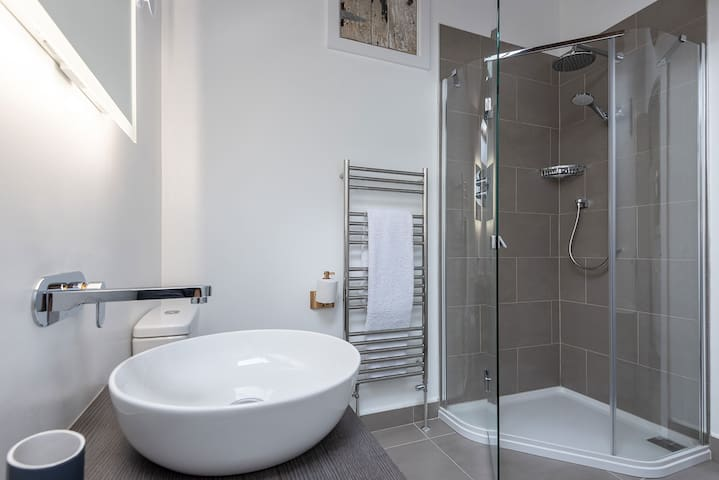 Shower, washbasin and Victoria and Albert bath in both en-suite bathrooms.