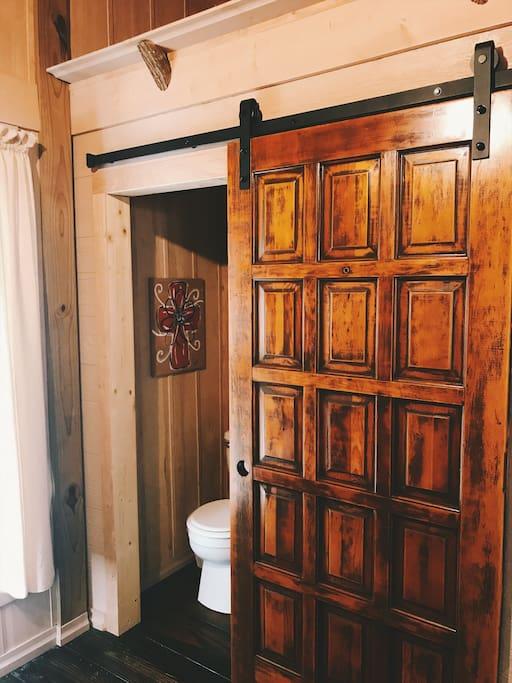 Bathroom with standup shower behind sliding barn door.