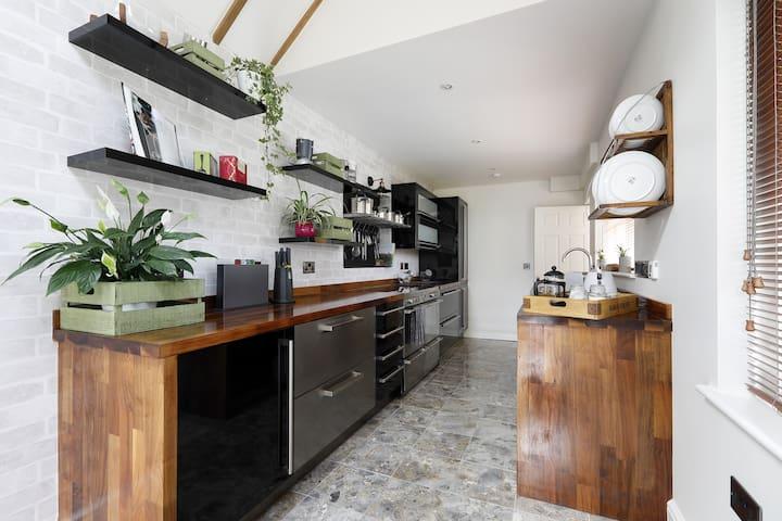 Range cooker with 3 ovens, large ceramic/halogen hob, double drawer fridge, separate freezer, washing machine and dishwasher.