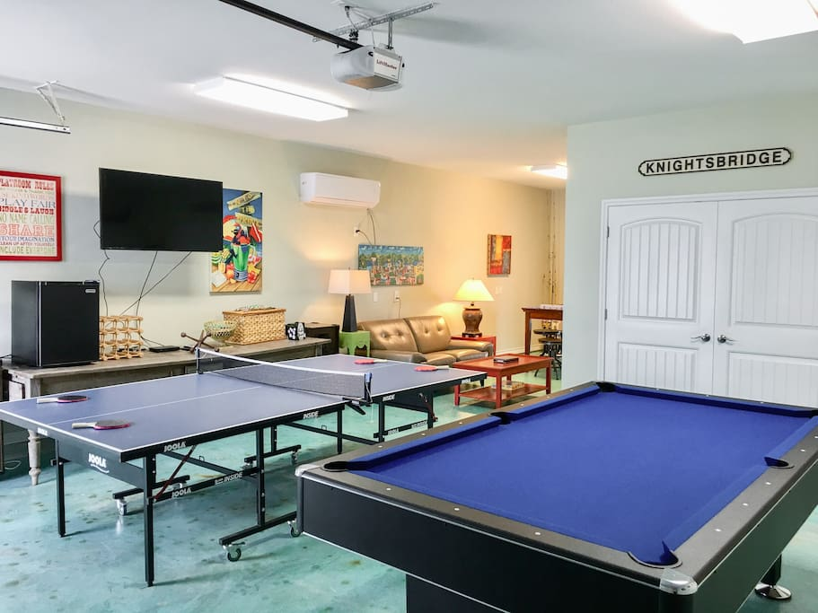 The entertainment room includes a pool and ping pong table as well as a flat screen TV and sofa.