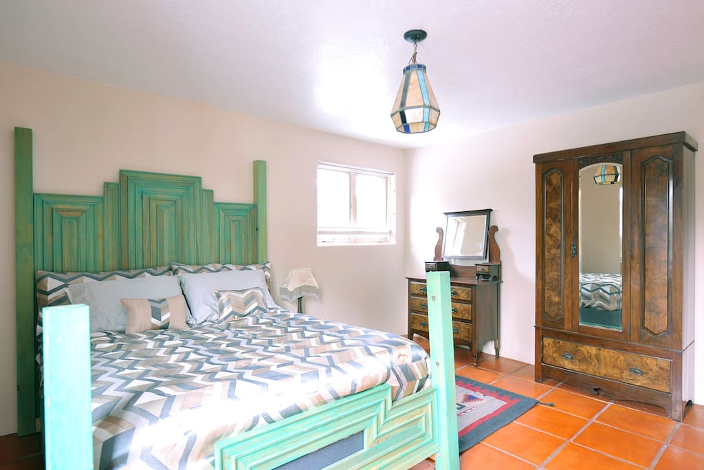 Spacious bedroom with a queen bed has two windows to enjoy the view of the pine trees