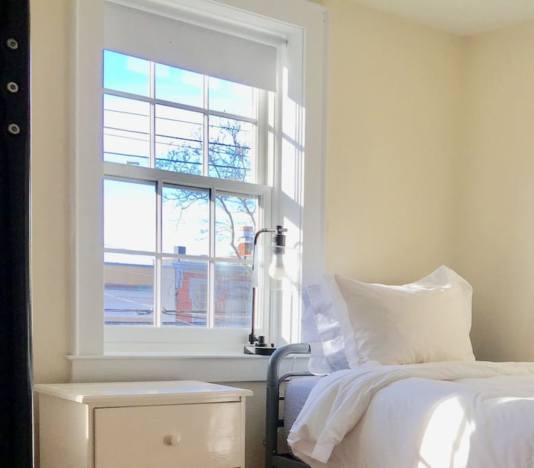 Freshly painted, front sunny bedroom with twin and bunk bed and a lovely view of Main Street.  Brand new white linens