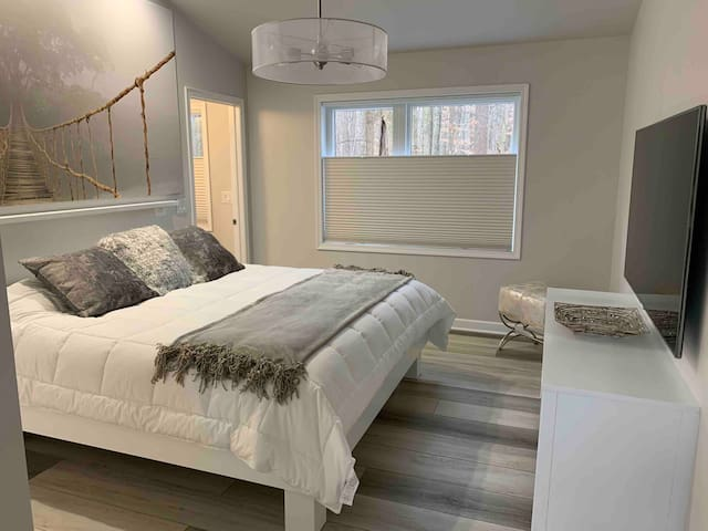 Cozy and inviting luxurious bedroom with plush hotel quality linens,  King size hybrid memory foam bed,  65 inch LED smart TV,  and Blackout top down-bottom up window shades for catching up on sleep anytime     day or night.
