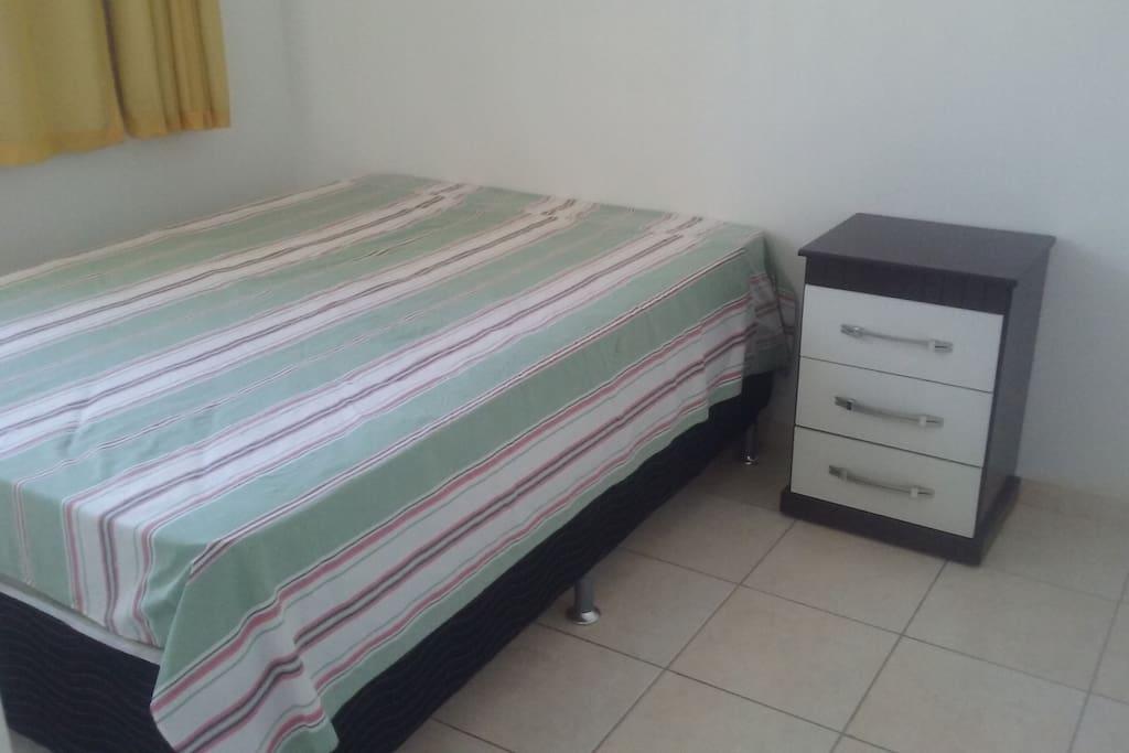 Quarto com cama de casal e cortina com black out