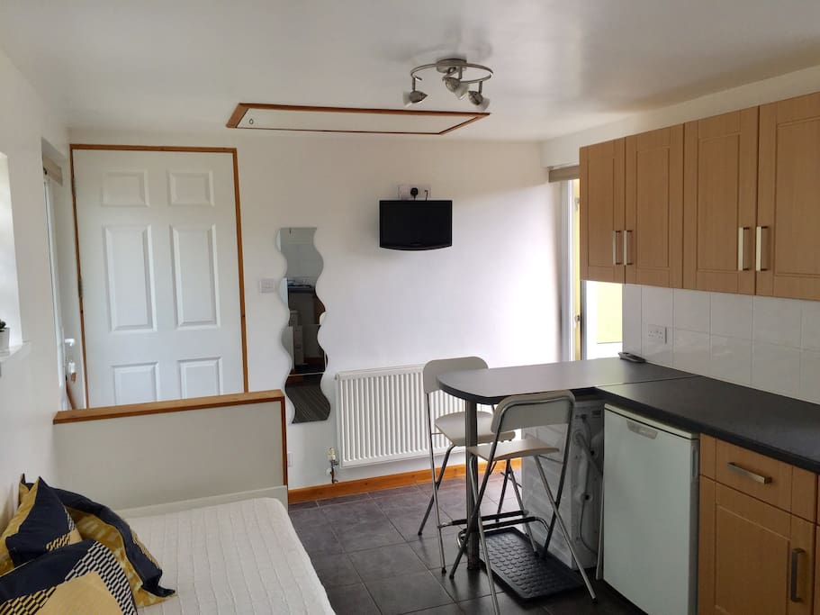 Looking towards the front and back doors. The flat comes with fridge freezer, washing machine and television.