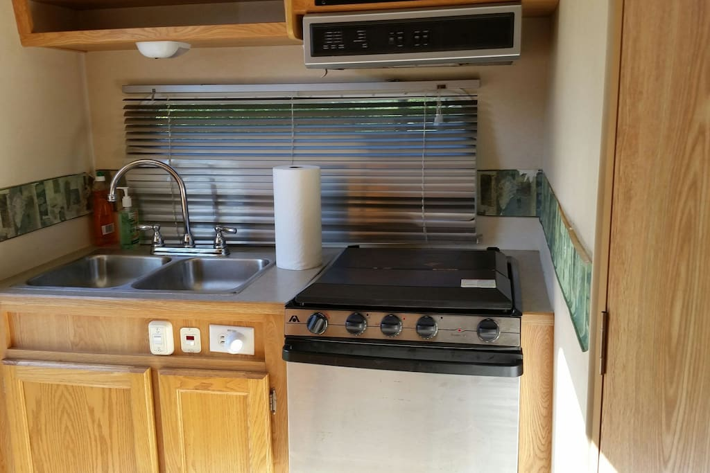 fully equipped kitchen with mirco, refrig, coffee pot, toaster, pots, pans, and 3 burner range with oven