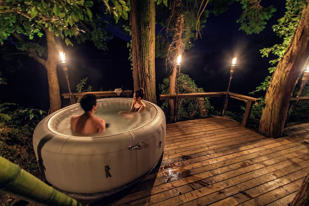 Guests enjoying the jacuzzi and torch-lit back deck