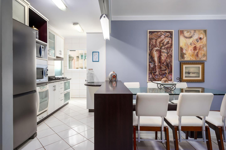 Cozinha americana completa incluindo máquina de lavar louça e geladeira duplex.  Contém utensílios domésticos, liquidificador, espremedor de frutas e batedeira elétrica. Churrasqueira a carvão em anexo.