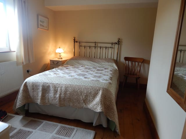 Double bedroom has wardrobe, chest of drawers , bedside table and lamp.