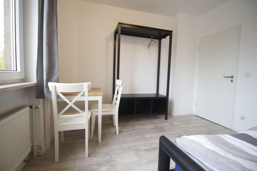 Zimmer mit Doppelbett, Tisch und Stühlen und Kleiderschrank