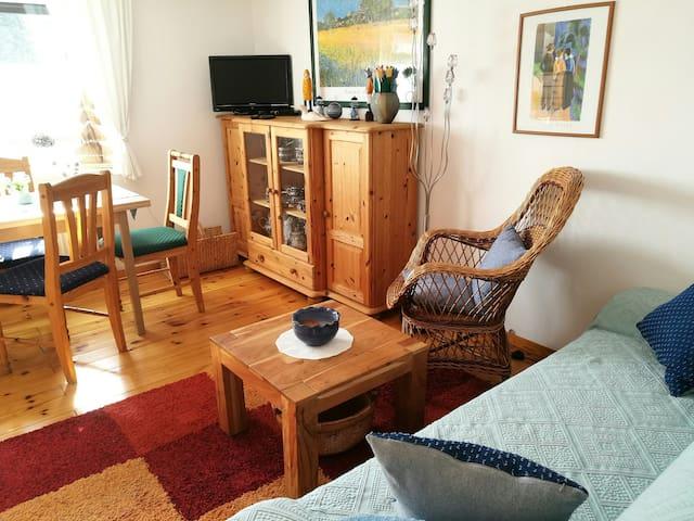 gemütliches Wohnzimmer mit Dielen und Kachelofen, rustikal eingerichtet