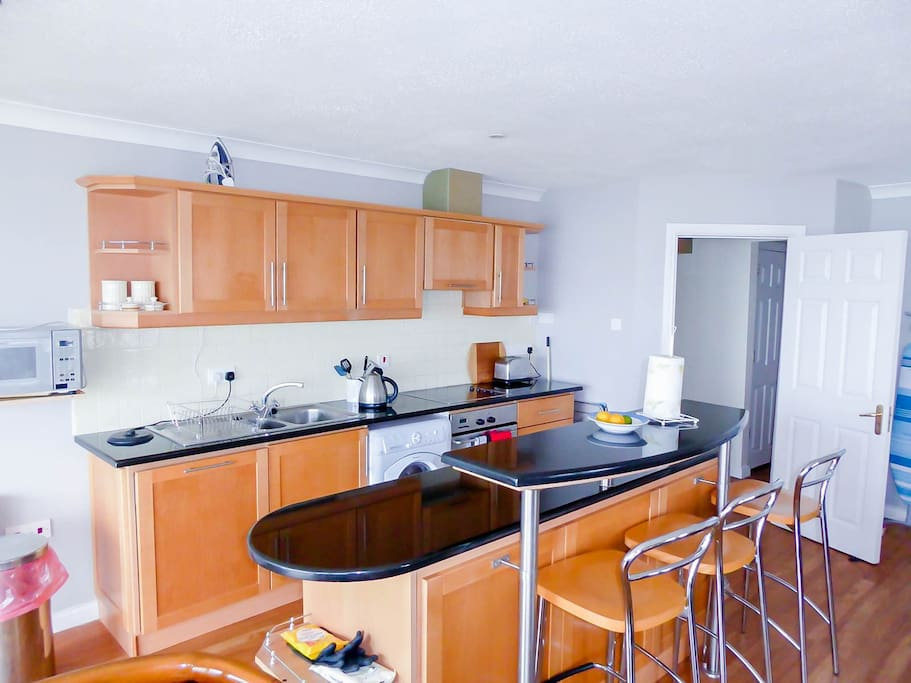 Kitchen with dishwasher, oven and hob, kettle, microwave, toaster, fridge and freezer.