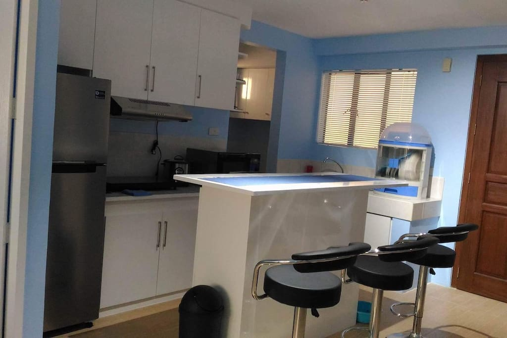 Kitchen and dining area with brand new appliances and brand new kitchen and dining wares.