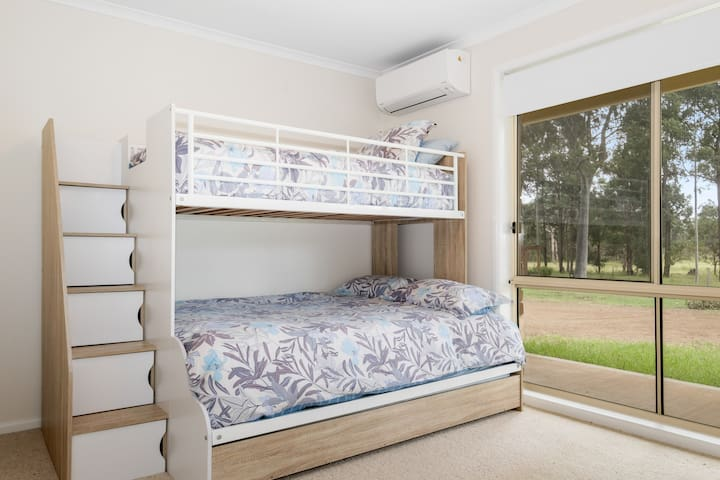 Bedroom with bunk beds. Single on top, double on bottom, and trundle bed. There is also a built in wardrobe and AC in the room, so you can heat or cool the room as you sleep.