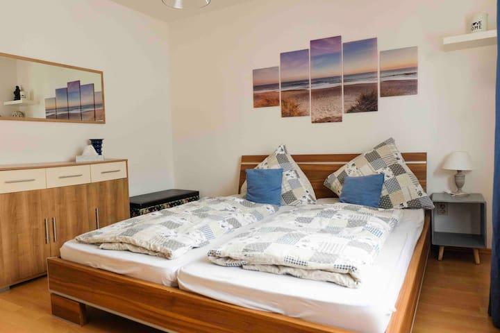 Schlafzimmer; lichtdurchflutetes Zimmer mit modernen Möbeln
