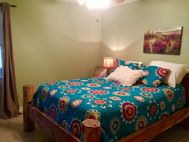Down stairs bedroom with queen bed and TV