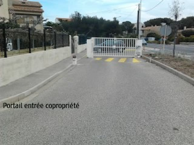 Entrée de la copropriété, portail sécurisé et place de parking