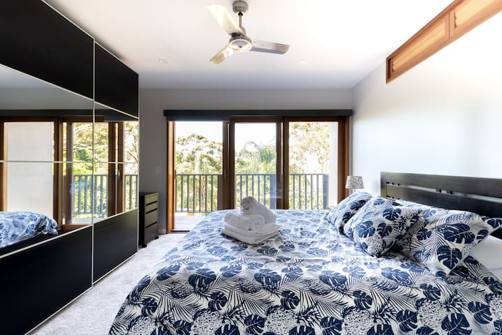 Master bedroom opens to an outside balcony overlooking local greenery and outside courtyard