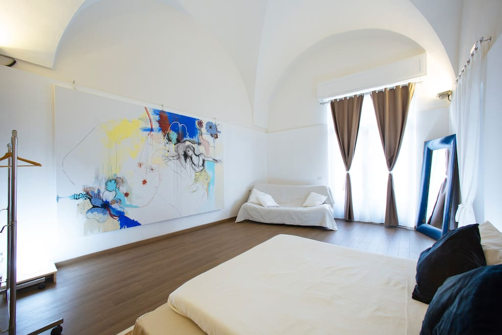 Very large bedroom with queen sized bed, high arched ceiling and original artwork on wall