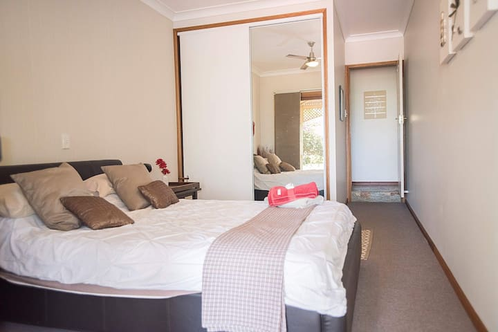Comfortable queen sized bed in private bedroom with double wardrobe and full length mirrors. Ceiling fan & heater available