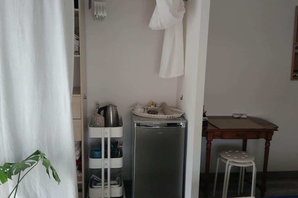 Chambre privée ; frigo, de quoi préparer thé et café, vaisselle à disposition dans petite desserte. Petite penderie au dessus avec cintre et derrière le rideau une étagère et un tirroire.