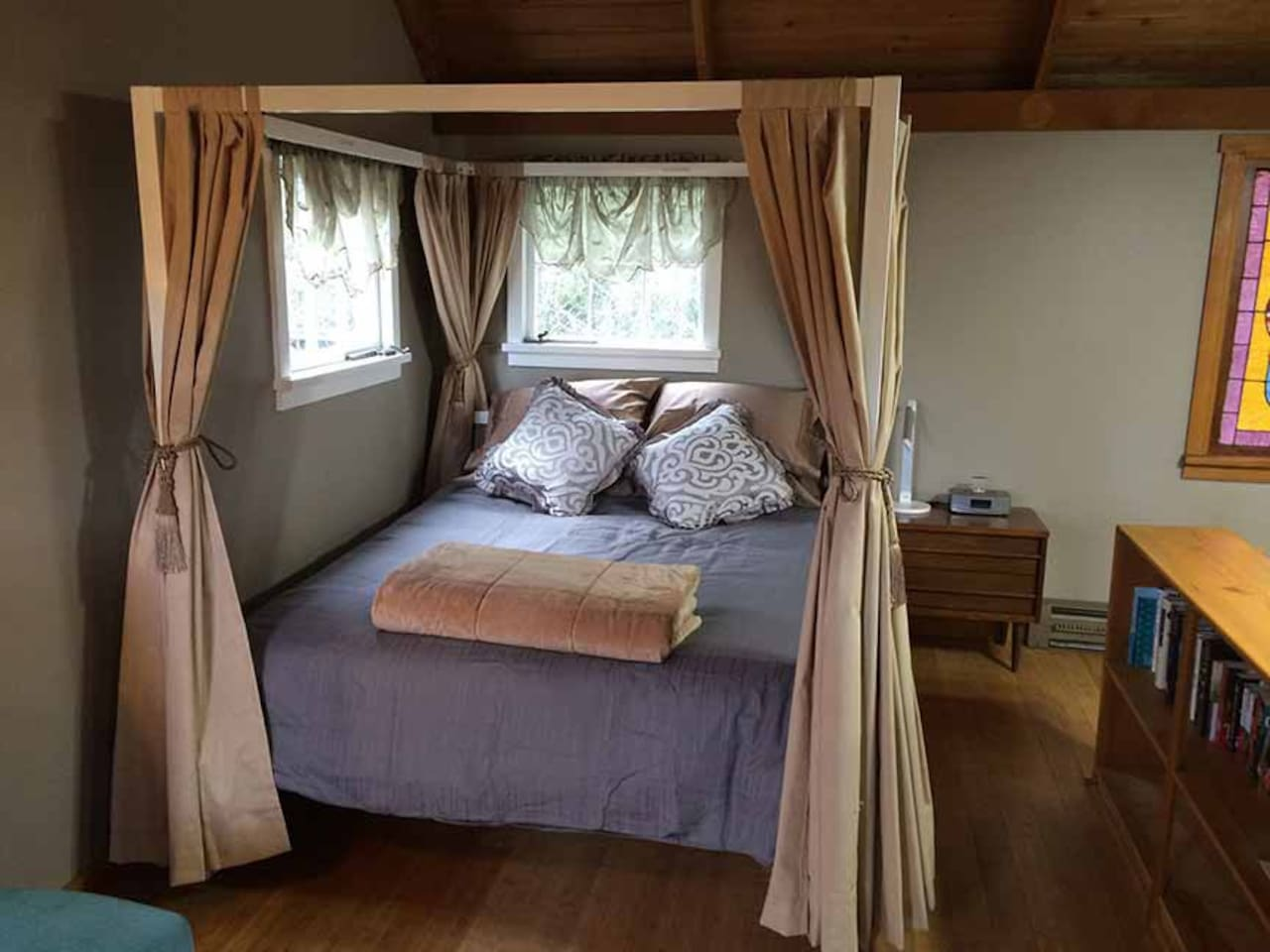Queen-size canopy bed with hypoallergenic comforter and pillows.  Bed curtains for privacy and light exclusion. Bedside lamp has USB port for charging devices. Radio/alarm clock/dock allows you to listen to your own music. Shelves are stocked with books, games, and puzzles.