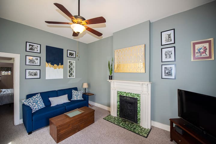 The living room exhibits New Orleans flair with a bright tiled fireplace and vintage New Orleans press photos.
