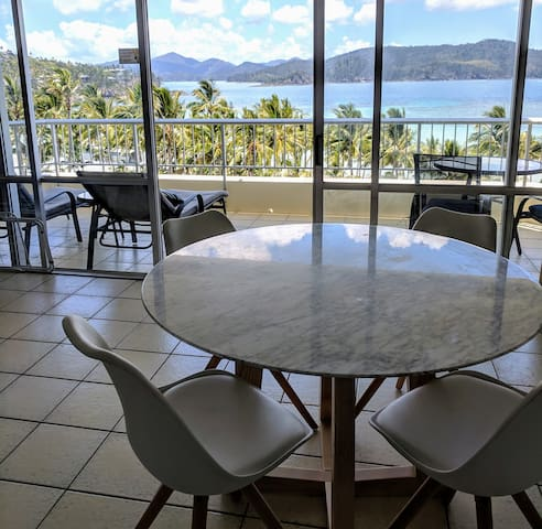 Large open-plan living and dining area, with views of the beach and islands from the balcony.